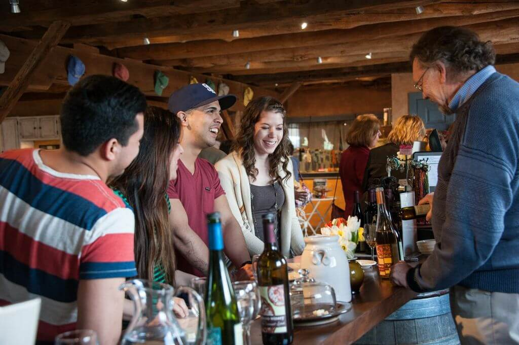A young group of people tasting and laughing at the tasting bar.