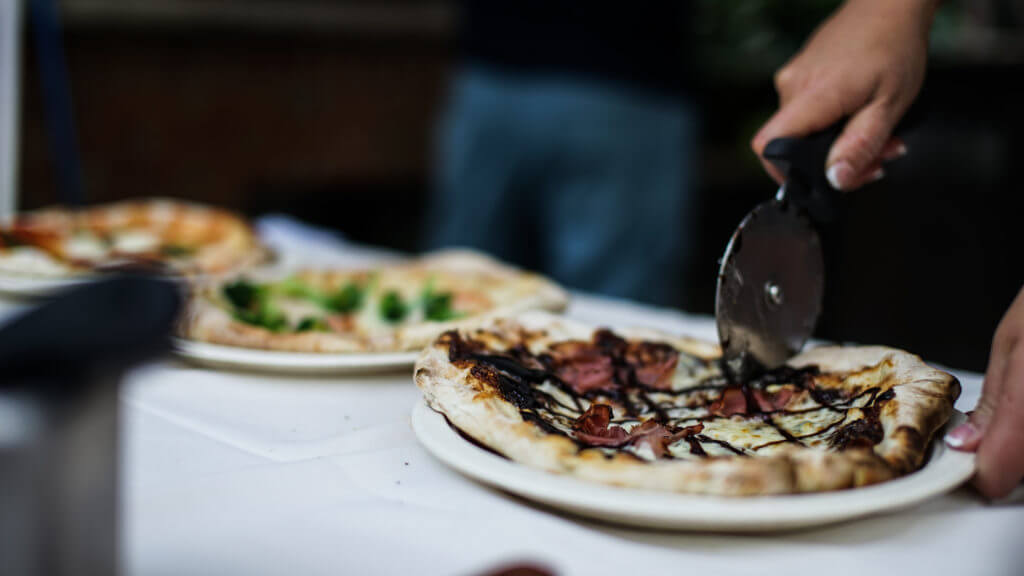 Cutting personal size pizzas glazed with balsamic drizzle.