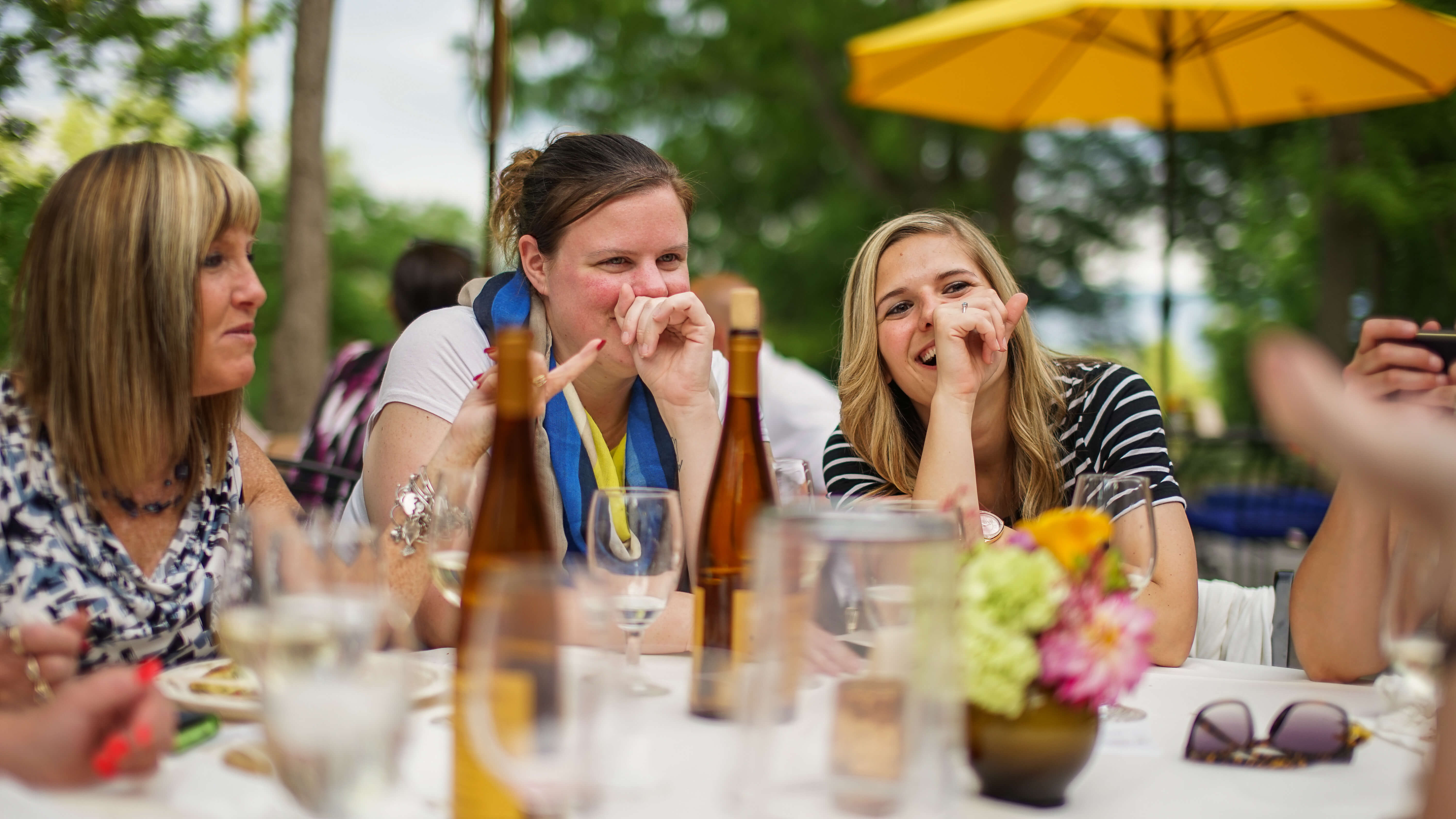 three girlfriends laughing at Pizza on the Patio event.