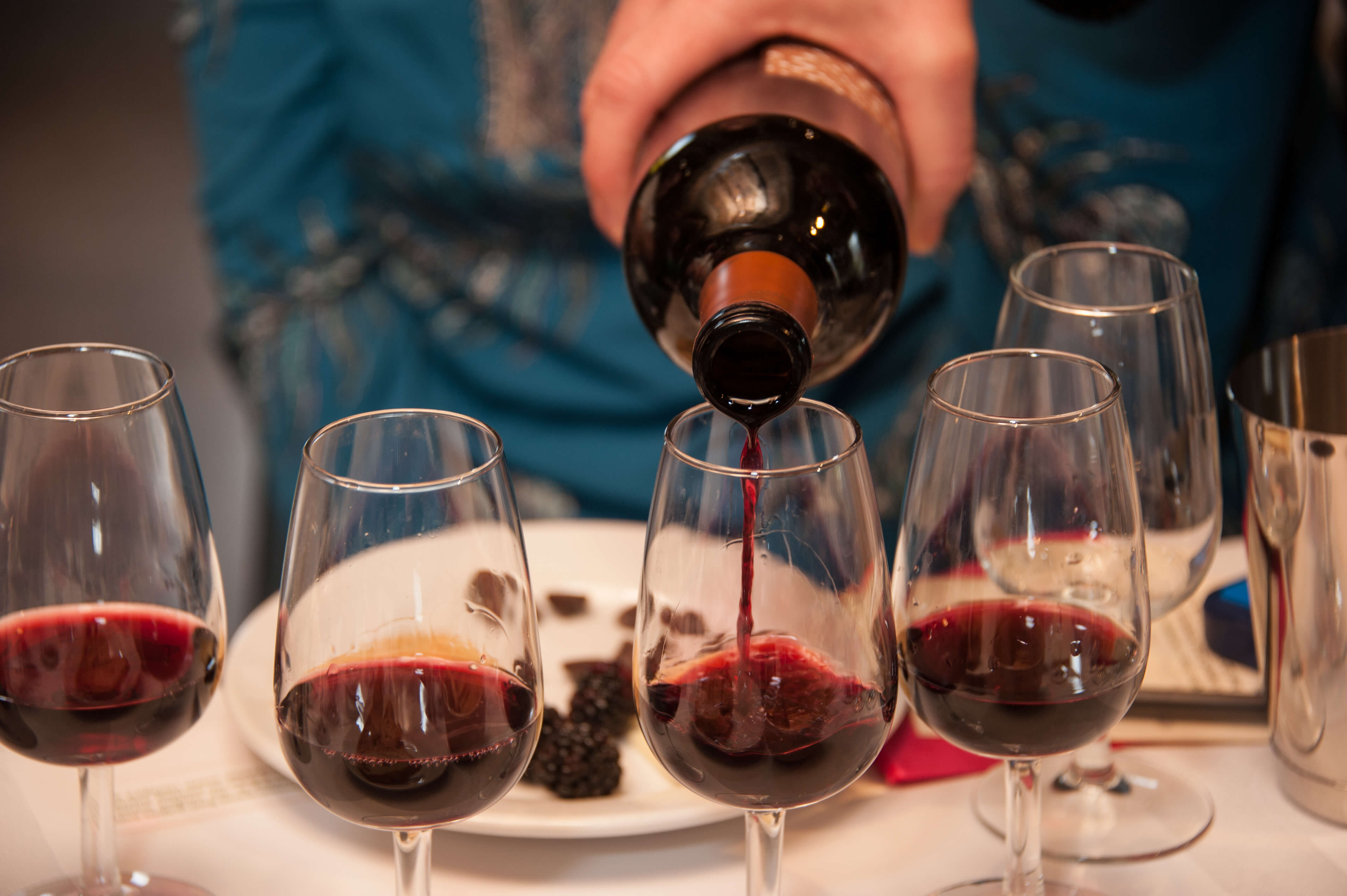 Five small glasses of red wine being poured for a vertical tasting event.