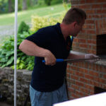 Man cooking with the brick pizza oven.