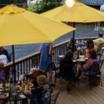 Guests enjoying the deck under the yellow umbrellas.