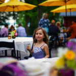 Little girl enjoying the patio with her parents.