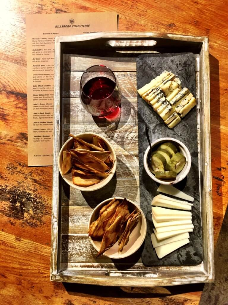 Sample Charcuterie board with cheese, wine, Saratoga Crackers, Garlic Pickles, and wine.