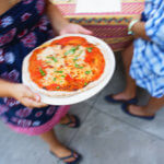 A guest wearing a blue dress picking up her individual pizza.